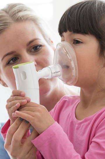 mother helping child using nebulizer with a mask