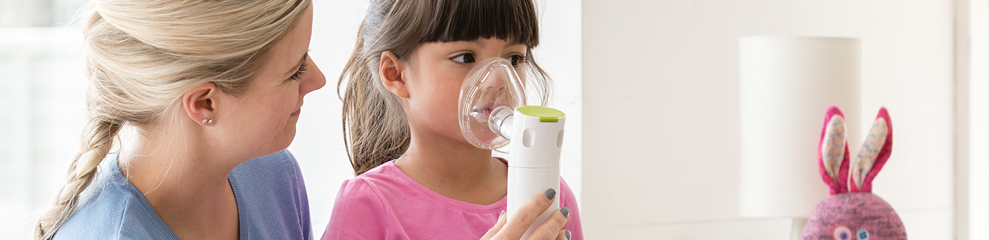 mother helping child with nebulizer